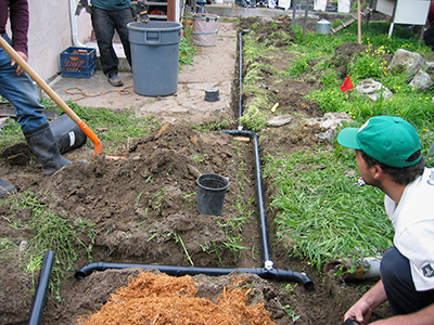 Laying pipe in trenches to direct water to the roots of plants.