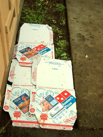 These pizza boxes are being used for sheet mulch to preserve moisture and keep weeds down.